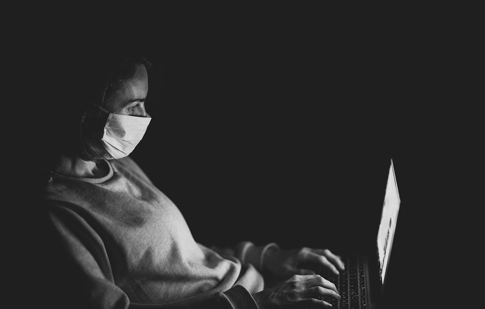 Woman sitting by computer sith mask on digital healthcare virtual